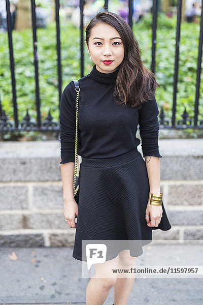 Porträt der modischen jungen Frau in schwarzem Pullover und Rock