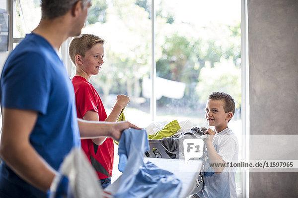 Jungen helfen dem Vater bei der Arbeit mit dem Wäschekorb.