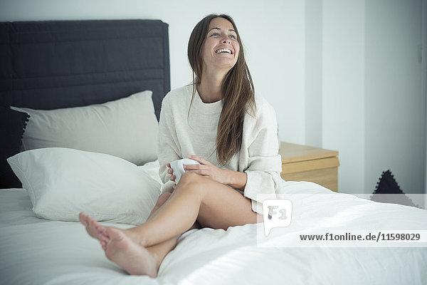 Fröhliche junge Frau auf dem Bett sitzend mit einer Tasse Kaffee