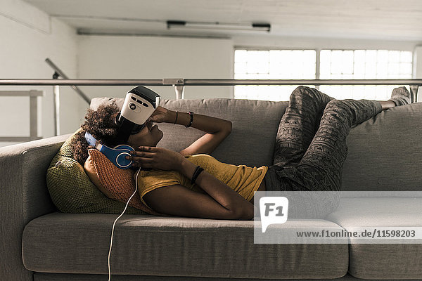 Young woman lying on couch with headphones and VR glasses