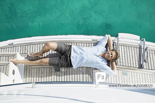 Lächelnder Mann auf Deck seiner Motoryacht liegend