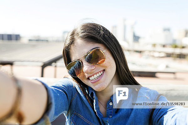 Portrait of smiling young woman wearing sunglasses taking selfie