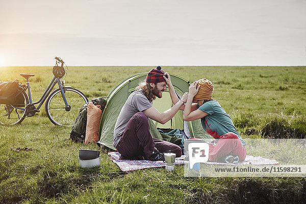 Deutschland  Schleswig-Holstein  Eiderstedt  verspieltes Paar mit Fahrrädern beim Zelten in Sumpflandschaft