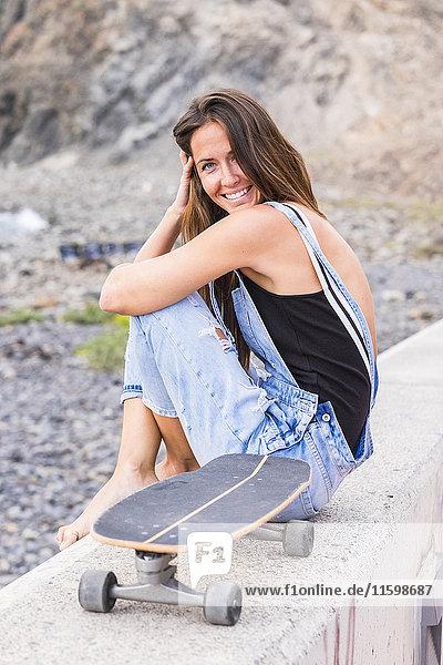 Porträt einer lächelnden Frau mit Skateboard auf einer Wand sitzend Porträt einer lächelnden Frau mit Skateboard auf einer Wand sitzend