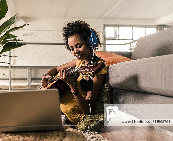Junge Frau zu Hause mit Kopfhörer und Laptop beim Gitarrespielen