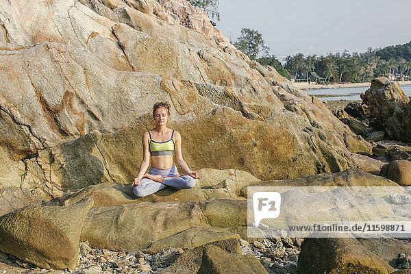 Frau sitzt im Lotussitz und meditiert am Strand.