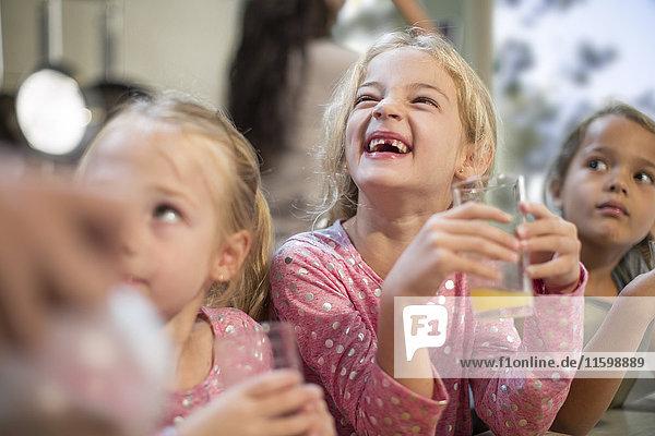 Mädchen trinken Fruchtsaft in der Küche