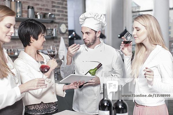 Chefkoch mit drei Frauen  die in der Küche Rotwein probieren