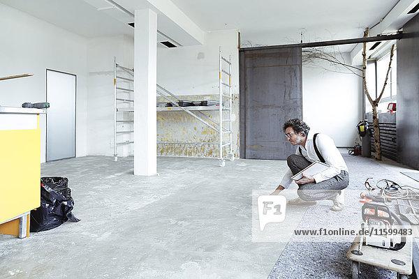 Architektin prüft Estrich auf der Baustelle