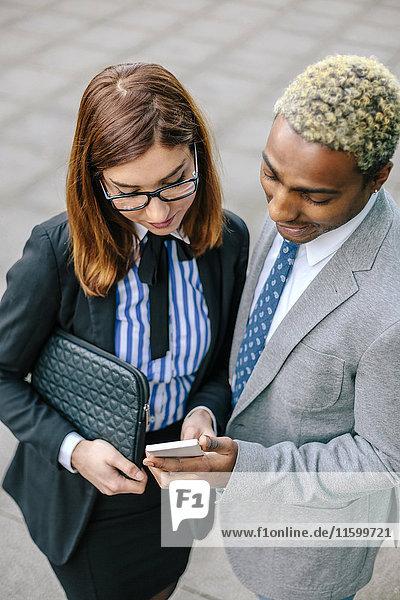 Ein junger Geschäftsmann und eine junge Frau  die auf ein Smartphone schauen.