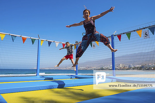 Verspielte Mutter und Sohn beim Trampolinfahren an der Küste Verspielte Mutter und Sohn beim Trampolinfahren an der Küste