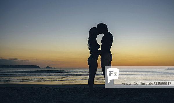 Junges Paar  das sich in der Abenddämmerung am Strand küsst.