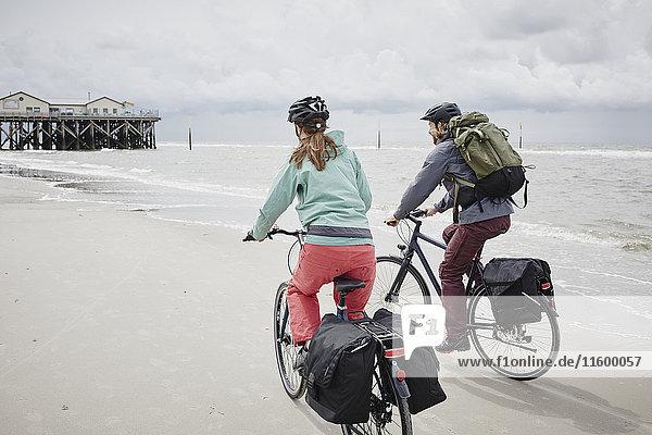 Deutschland  Schleswig-Holstein  St. Peter-Ording  Paar Radfahren am Strand