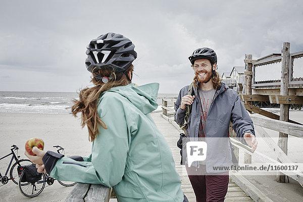 Deutschland  Schleswig-Holstein  St. Peter-Ording  Paar auf einer Fahrradtour mit Pause am Steg am Strand Deutschland, Schleswig-Holstein, St. Peter-Ording, Paar auf einer Fahrradtour mit Pause am Steg am Strand