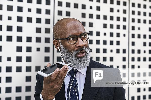 Mature businessman talking on the phone  wearing earphones