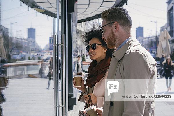 Paar in der Stadt mit Kaffee zum Mitnehmen im Schaufenster