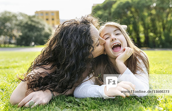 Mother and daughter having fun lying in the grass