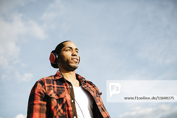 Porträt eines jungen Mannes  der Musik mit Kopfhörern vor dem Himmel hört.
