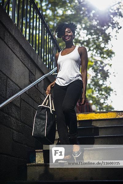 Porträt einer lächelnden Frau beim Treppensteigen