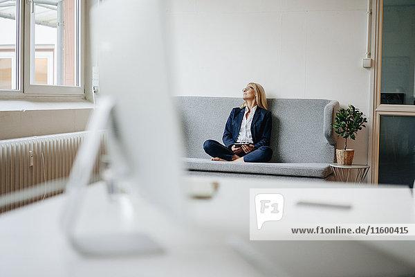 Entspannte Geschäftsfrau auf der Couch sitzend