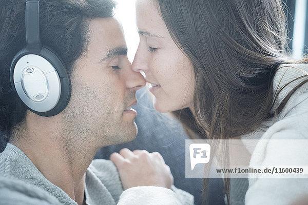 Junge Frau küsst Mann mit Kopfhörer zu Hause