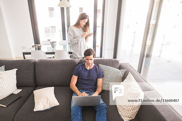 Junges Paar zu Hause mit Handy und Laptop