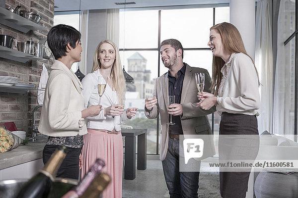 Freunde mit Champagnergläsern in einer Stadtwohnung
