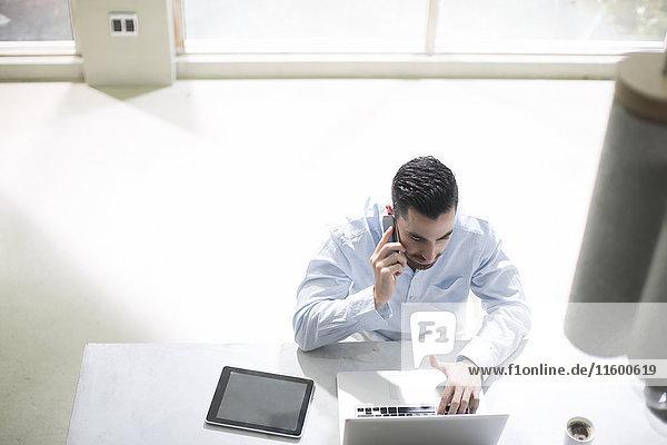 Jungunternehmer im Büro  der mit mobilen Geräten arbeitet