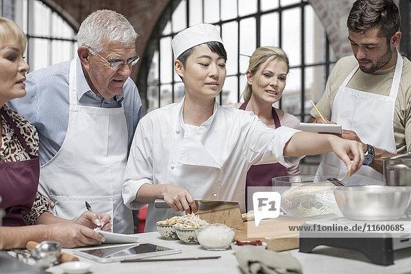 Die Teilnehmer des Kochkurses beobachten die Köchin beim Kochen.