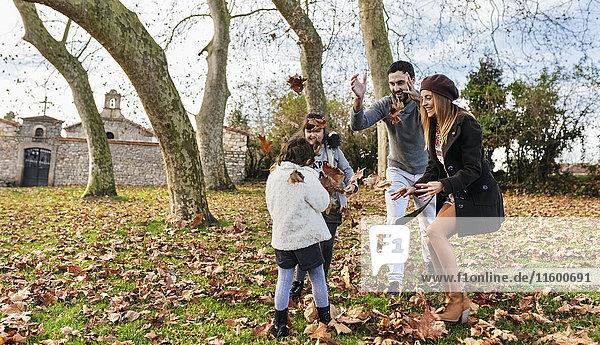 Familienspiel mit Herbstblättern im Park