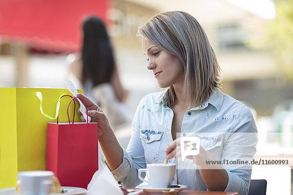 Frau mit Einkaufstaschen in einem Außencafé  die die Rechnung prüft