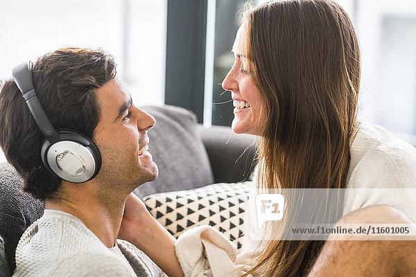 Lächelnde junge Frau  die den Mann mit Kopfhörer zu Hause ansieht.