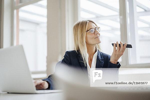 Geschäftsfrau mit Laptop und Handy im Büro