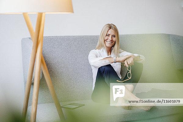 Porträt einer lächelnden  entspannten Geschäftsfrau  die auf der Couch sitzt.