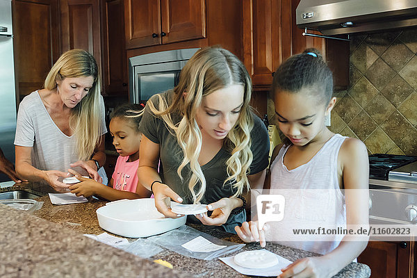 Mother and daughters cooking in domestic kitchen