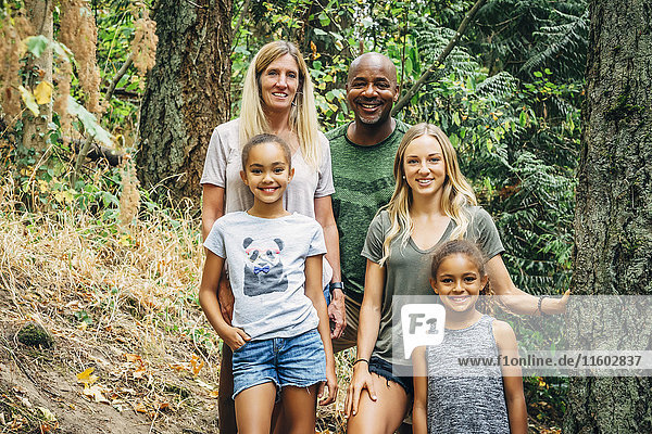 Multi-ethnic family posing in forest