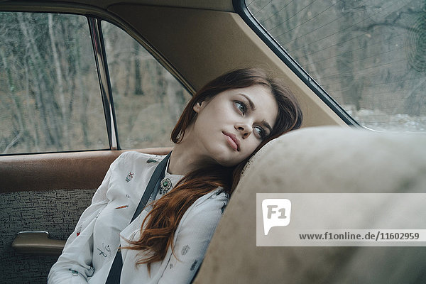 Caucasian woman in back seat of car looking out window