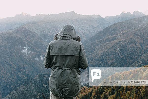 Caucasian man wearing coat looking at valley