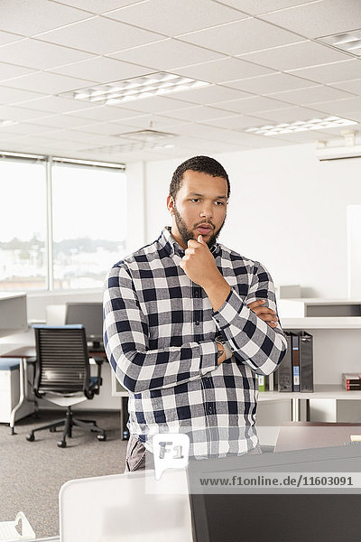 Pensive Mixed Race man standing in office