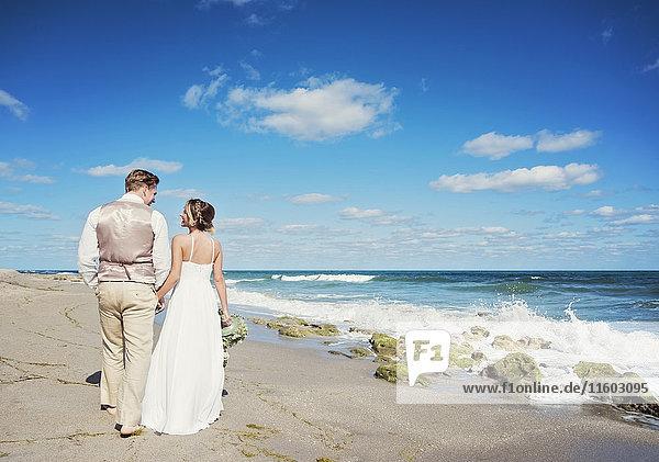 Caucasian bride and groom walking on beach
