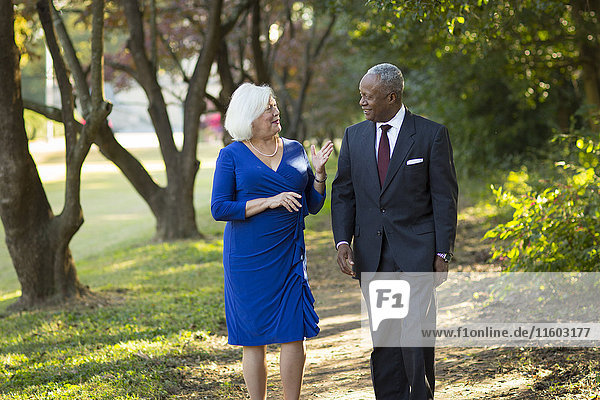 Couple walking and talking on path in park