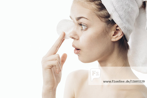 Surprised Caucasian woman cleaning skin with pad