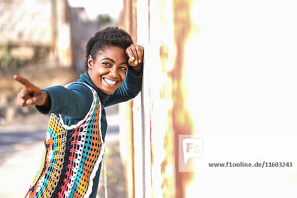 Smiling African American woman leaning on wall and pointing finger