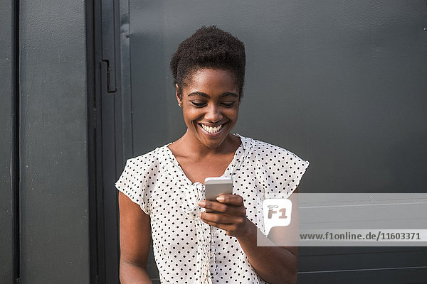 Smiling African American woman texting on cell phone