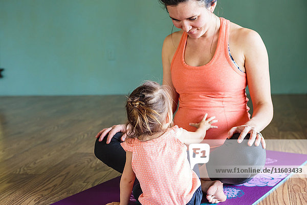 Mixed Race girl touching belly of expectant mother on exercise mat