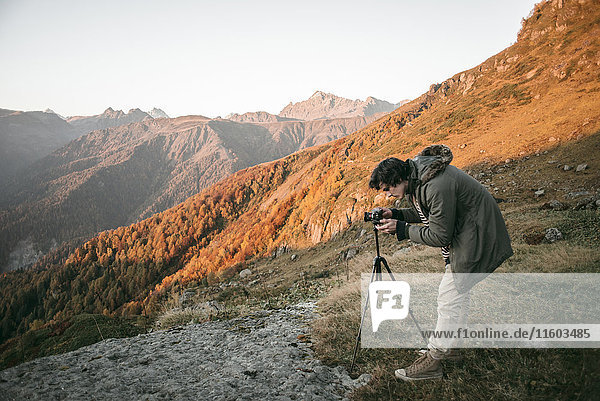 Caucasian man photographing valley from mountain