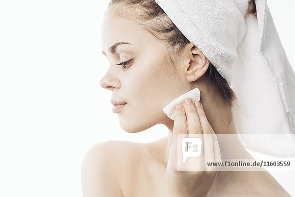 Caucasian woman cleaning chin with pad