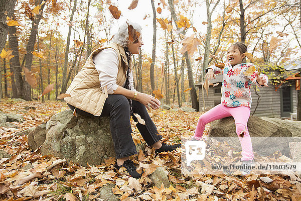 Grandmother and granddaughter playing with autumn leaves