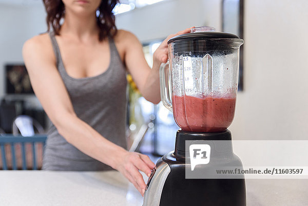 Caucasian woman mixing fruit smoothie in blender
