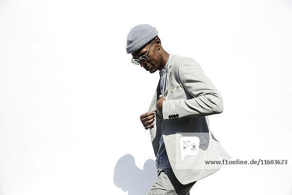 Black man wearing sunglasses adjusting jacket